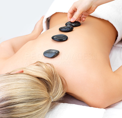 Buy stock photo Young woman relaxing face down having hot stones placed in a row down her back at a health spa