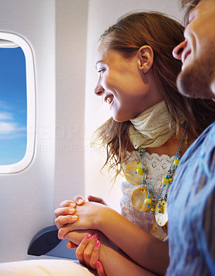 Buy stock photo An attractive young couple sitting in an airplane