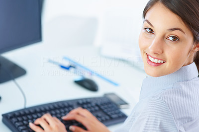 Buy stock photo Closeup of female executive typing on keyboard and giving you cute smile