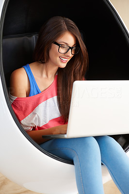 Buy stock photo Smiling young girl sitting in an egg chair using laptop