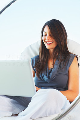 Buy stock photo Attractive young woman sitting on an egg chair using laptop