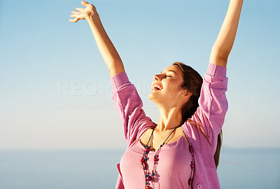 Buy stock photo Pretty young woman standing against sky with hands raised