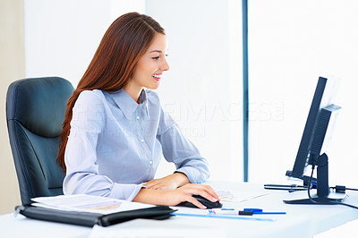 Buy stock photo Smiling businesswoman sitting at an office table and working on computer
