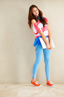 Buy stock photo Full length of cute young girl standing near wall with laptop and headphones and smiling