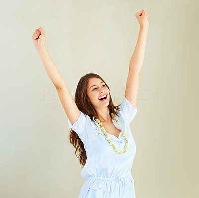 Buy stock photo Excited young woman with arms raised against plain background
