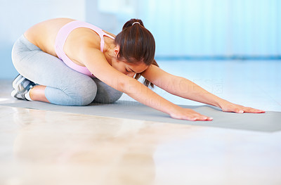 Buy stock photo Young woman practicing yoga on her mat at the gym - copyspace
