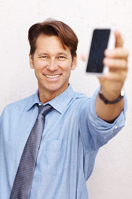 Buy stock photo Portrait of a happy young businessman showing a cellphone