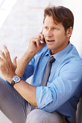 Buy stock photo Portrait of a confused young male executive sitting on ground and using cellphone