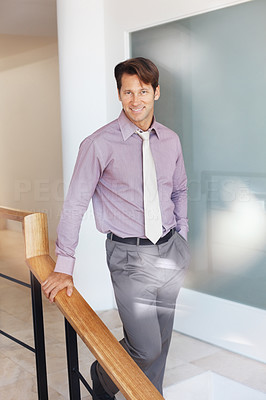 Buy stock photo Portrait of a smart young male business executive walking down the stairs