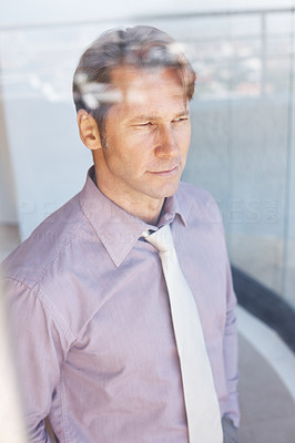 Buy stock photo Portrait of a successful young businessman looking through window