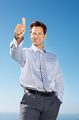 Buy stock photo Portrait of a successful young businessman gesturing thumbs up sign against sky