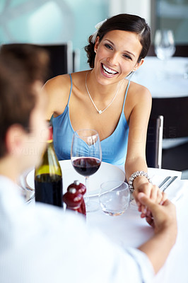 Buy stock photo Smiling young beautiful lady holding hand with her boyfriend at arestaurant