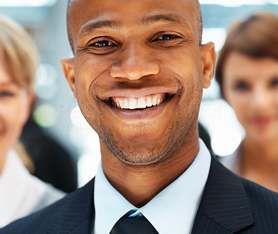 Buy stock photo Closeup of businessman smiling with colleagues in background