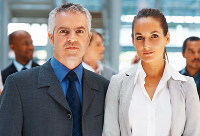 Buy stock photo Business man and woman standing together with colleagues in background