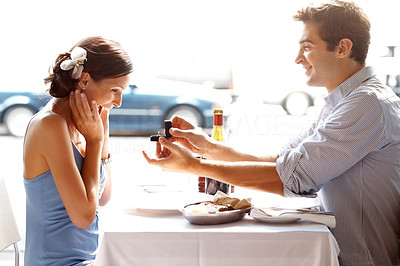 Buy stock photo Happy young man proposing to his delighted girlfriend at a brighlty lit restaurant table