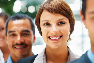 Buy stock photo Focus on pretty businesswoman with colleagues in front and back of her