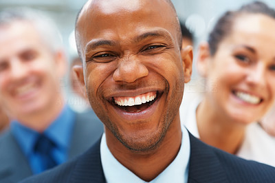 Buy stock photo Closeup of happy businessman with smiling colleagues behind him