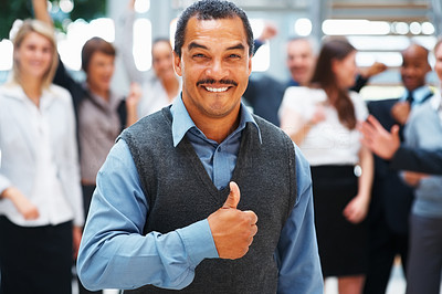 Buy stock photo View of businessman giving thumbs up with exuberant team in background