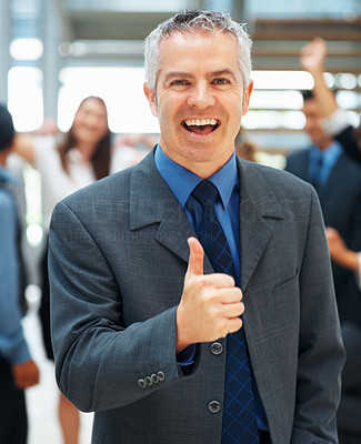 Buy stock photo Executive giving thumbs up with excited colleagues in background