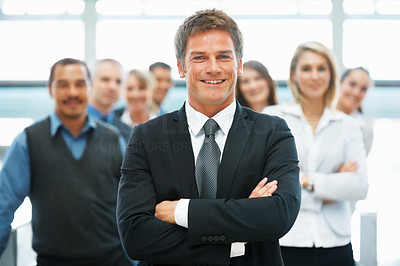 Buy stock photo Portrait of handsome executive with arms crossed and colleagues in background