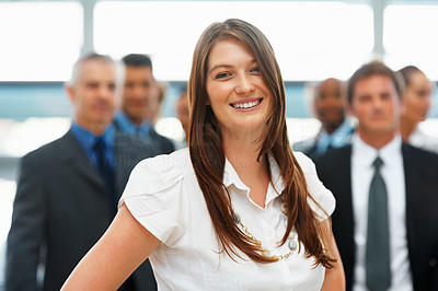Buy stock photo Young female executive with colleagues in background
