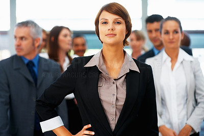 Buy stock photo Confident female executive with colleagues in distance