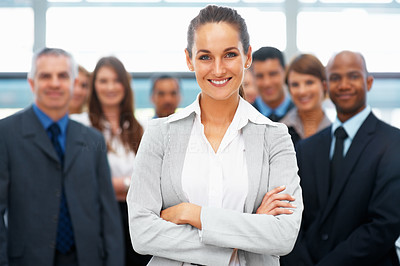 Buy stock photo Pretty businesswoman standing with colleagues indoors