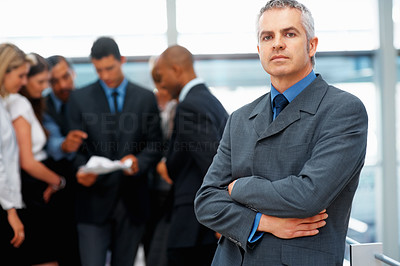 Buy stock photo Serious male executive with team discussing proposal in distance