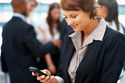Buy stock photo Young female executive texting on mobile phone