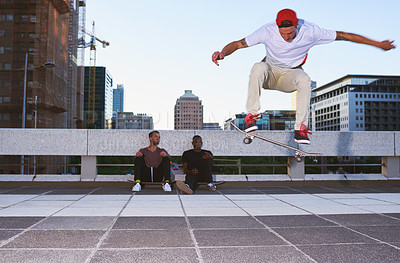 Buy stock photo Shot of a young man doing tricks on his skateboard while his friends looks on