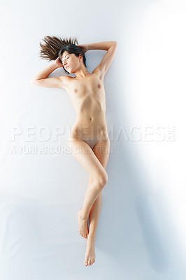 Buy stock photo Shot of a beautiful naked woman lying on the studio floor