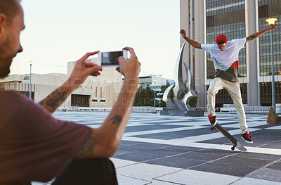 Buy stock photo Shot of a man taking a picture of his friend doing tricks on his skateboard