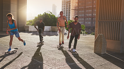 Buy stock photo Shot of a group of skaters skating in the city