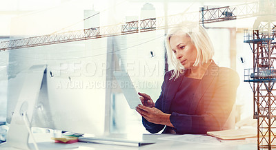 Buy stock photo Shot of a businesswoman at her desk superimposed over a cityscape