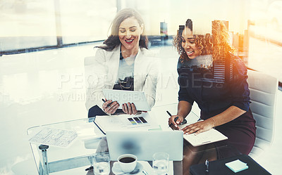 Buy stock photo Shot of two businesswomen using a tablet superimposed over a cityscape