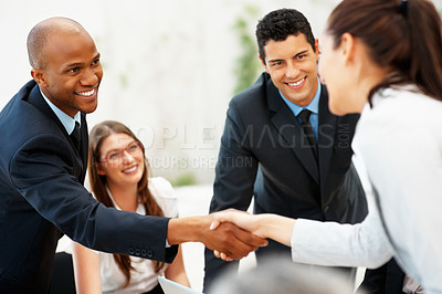 Buy stock photo View of executives shaking hands while colleagues smile