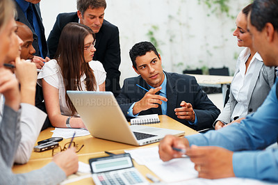 Buy stock photo Confident male executive explaining project to colleagues during meeting
