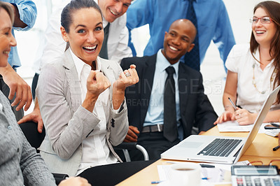 Buy stock photo Excited business woman clenching her fists with colleagues look on