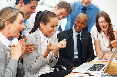 Buy stock photo Excited female executive clenching her fists while colleagues look on