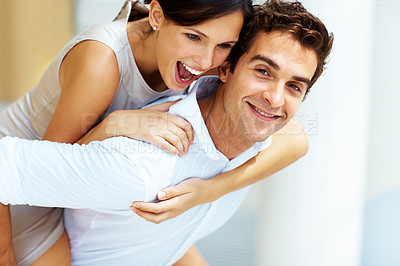 Buy stock photo Portrait of happy young male piggybacking his cute girlfriend smiling