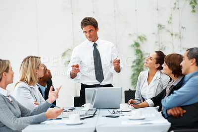Buy stock photo Executive in charge of meeting standing up while colleagues are seated
