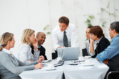 Buy stock photo Business people sitting around the table having meeting