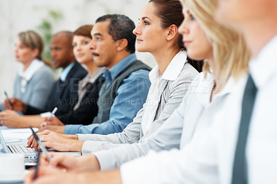 Buy stock photo Focus on woman listening attentively during business presentation with colleagues