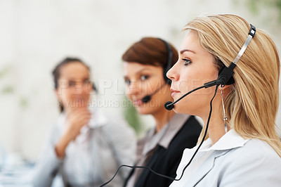 Buy stock photo Focus on call center employee with colleagues in background