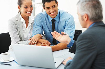 Buy stock photo Smiling business couple having a discussion with mature executive