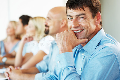 Buy stock photo Happy mature businessman sitting in a conference with his colleagues at office