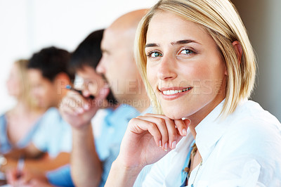 Buy stock photo Closeup of a pretty young businesswoman smiling in a meeting with her colleagues in background