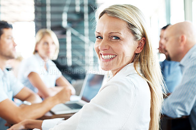Buy stock photo Portrait of cheerful young businesswoman in a business meeting smiling with colleagues at the back