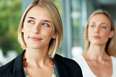 Buy stock photo Portrait of a thoughtful young businesswoman standing with colleague in background