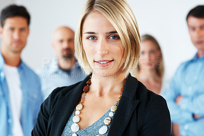 Buy stock photo Group of business colleagues standing behind a pretty young woman